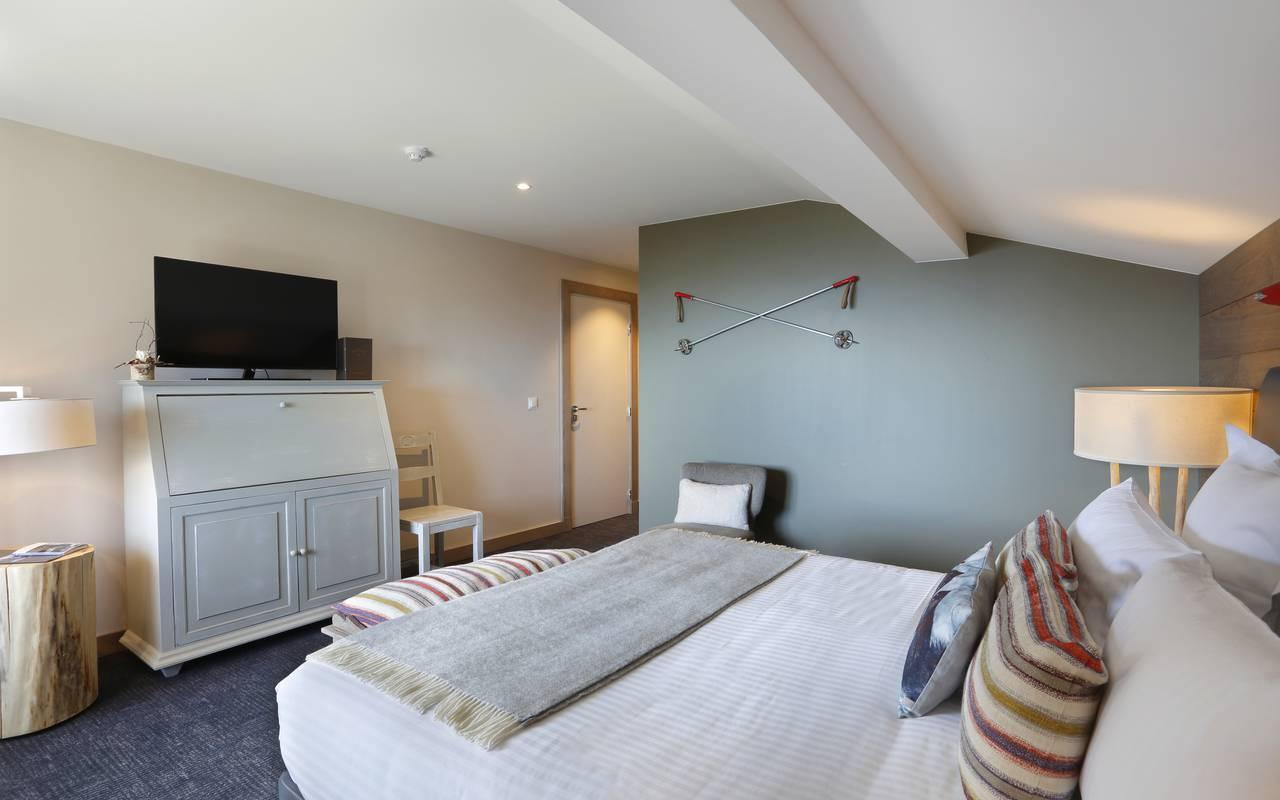 Suite lodge avec lit double confortable et une télévision, hotel luxe jura, La Mainaz.