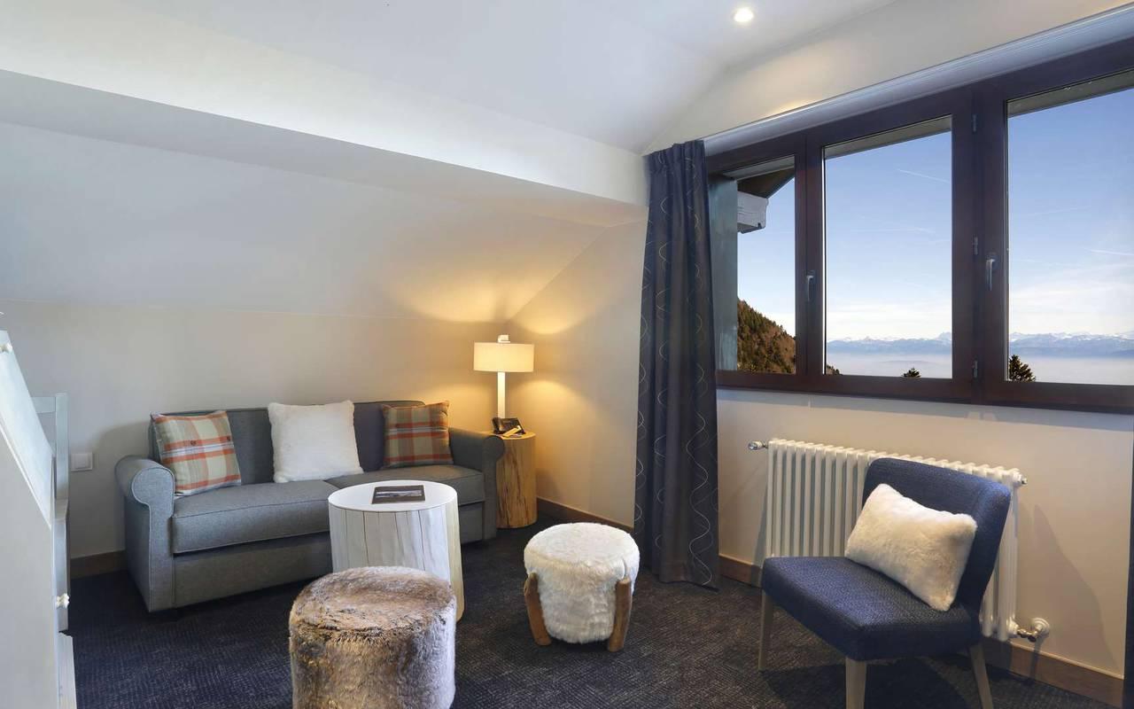 Petit salon cosy avec canapé et une belle vue sur l'extérieur, hotel de luxe haut jura, La Mainaz.